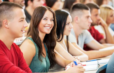 Group of students sitting and listening to a lecture. The focus is on the girl looking at camera.
