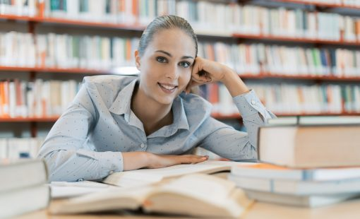 Smiling female student at the library, she is sitting at desk and studying, education and self improvement concept